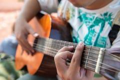 演奏演奏与吉他的吉他…美丽的青少年的女孩音乐 免版税库存图片