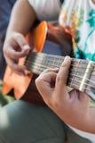 演奏演奏与吉他的吉他…美丽的青少年的女孩音乐 免版税图库摄影