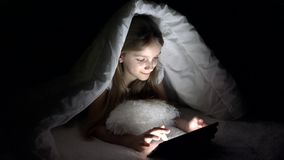 演奏片剂在黑暗的夜,女孩浏览互联网的孩子在床上,不睡觉 影视素材