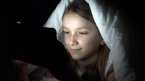 演奏片剂在黑暗的夜,女孩浏览互联网的孩子在床上,不睡觉 股票录像
