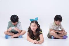 演奏片剂的亚洲孩子 图库摄影