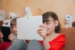 演奏片剂的女孩5和7岁 免版税图库摄影