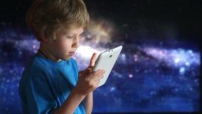 演奏片剂的男孩个人计算机 男孩和片剂设备在手上坐宇宙天空背景  影视素材