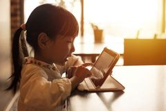 演奏片剂计算机的亚裔中国小女孩 库存图片