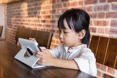 演奏片剂计算机的亚裔中国小女孩 免版税库存照片