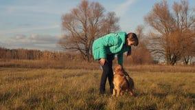 演奏狗的十几岁的女孩在秋天草甸 走在秋天的家庭在有狗的公园 股票录像