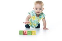 演奏玩具块的愉快的孩子隔绝在白色背景 库存照片