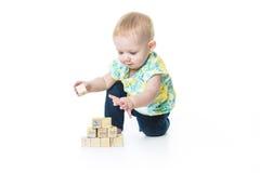 演奏玩具块的愉快的孩子隔绝在白色背景 免版税库存照片