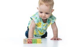 演奏玩具块的愉快的孩子隔绝在白色背景 免版税库存图片
