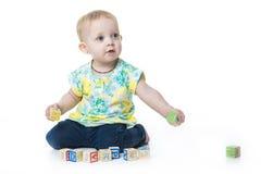 演奏玩具块的愉快的孩子隔绝在白色背景 免版税图库摄影