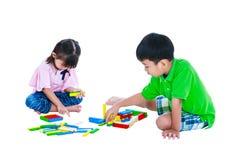 演奏玩具木刻的孩子,隔绝在白色背景 免版税库存图片