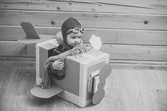 演奏玩具的孩子 使用与纸板飞机的小逗人喜爱的男孩 免版税库存图片