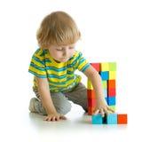 演奏玩具的小男孩隔绝在白色背景 免版税库存照片