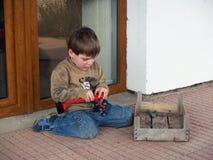 演奏玩具的男孩汽车 免版税图库摄影
