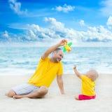 演奏玩具飞机的婴孩和父亲 免版税库存图片