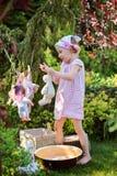演奏玩具洗涤在夏天庭院里和垂悬玩具的逗人喜爱的愉快的儿童女孩 免版税库存图片
