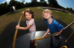 演奏环形交通枢纽年轻人的男孩女孩 免版税库存图片