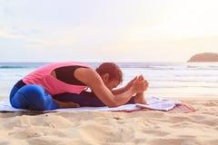 演奏瑜伽和锻炼在热带海滩的妇女在Thailan 图库摄影