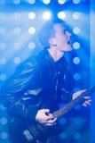 演奏电吉他和唱歌的年轻岩石音乐家 在聚光灯背景的摇滚明星  免版税库存照片