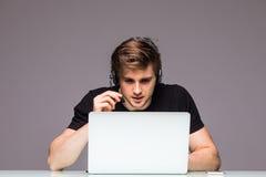 演奏电子游戏佩带的耳机的年轻游戏玩家和讲话 免版税库存照片