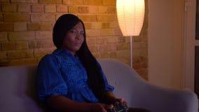 演奏电子游戏和失败的成人非裔美国人的女性特写镜头射击是被挫败的坐长沙发 股票录像