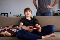 演奏电子游戏控制台的愉快的年轻男孩供以座位在沙发,当他的父亲身分接近在客厅在家时 免版税库存照片