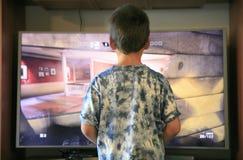 演奏电子游戏控制台的男孩 免版税图库摄影