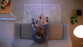 演奏电子游戏电视的年轻便服男性特写镜头顶面射击使用比赛控制台坐长沙发 股票视频