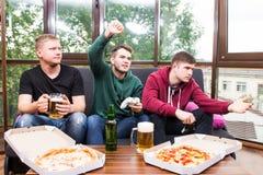 演奏电子游戏,饮料啤酒的男性朋友和在家获得乐趣 免版税库存照片