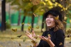 演奏秋天叶子的女孩 免版税库存图片