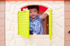 演奏窗口玩具房子的愉快的亚裔儿童男孩在操场 免版税库存照片