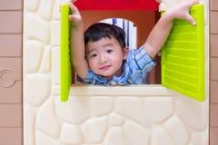 演奏窗口玩具房子的愉快的亚裔儿童男孩在操场 免版税图库摄影