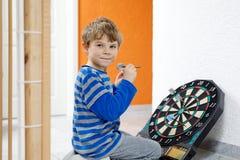 演奏箭的小逗人喜爱的白肤金发的学龄前孩子男孩,户内 免版税图库摄影