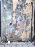 演奏篮球`的街道墙壁上的标题`孩子 免版税库存照片