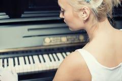 演奏纵向减速火箭的样式妇女的钢琴 免版税图库摄影