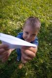 演奏纸飞机的逗人喜爱的白种人孩子在公园户外在夏天晴天 图库摄影