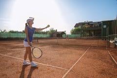 演奏网球和服务的美丽的年轻女人 免版税库存图片