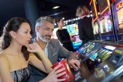 演奏老虎机的夫妇在赌博娱乐场 免版税图库摄影