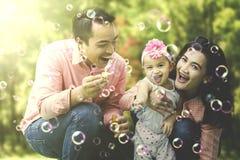 演奏肥皂泡的快乐的家庭 图库摄影