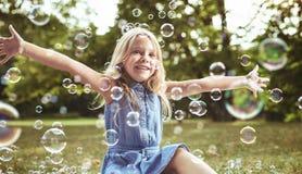 演奏肥皂泡的逗人喜爱的小女孩 库存图片