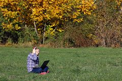 演奏膝上型计算机和听的音乐在headphon的小女孩 免版税图库摄影