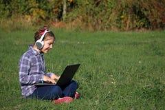 演奏膝上型计算机和听的音乐在headphon的小女孩 免版税库存图片
