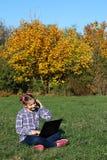 演奏膝上型计算机和谈话在智能手机的小女孩 库存照片