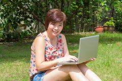 演奏膝上型计算机的亚裔妇女在庭院里 免版税库存照片