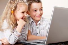 演奏膝上型计算机的孩子 图库摄影