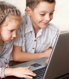 演奏膝上型计算机的孩子 免版税库存图片