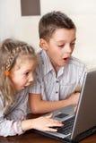 演奏膝上型计算机的孩子 库存图片