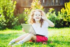 演奏膝上型计算机的逗人喜爱的女孩,坐绿草在夏天p 库存照片