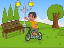 演奏自行车的小男孩在公园动画片 库存照片