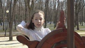 演奏船长的女孩在一艘木船的舵在操场的在春天公园 她调直她 股票录像